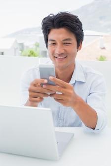 Homem feliz usando seu laptop e mensagens de texto no telefone