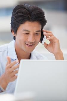 Homem feliz usando seu laptop falando ao telefone