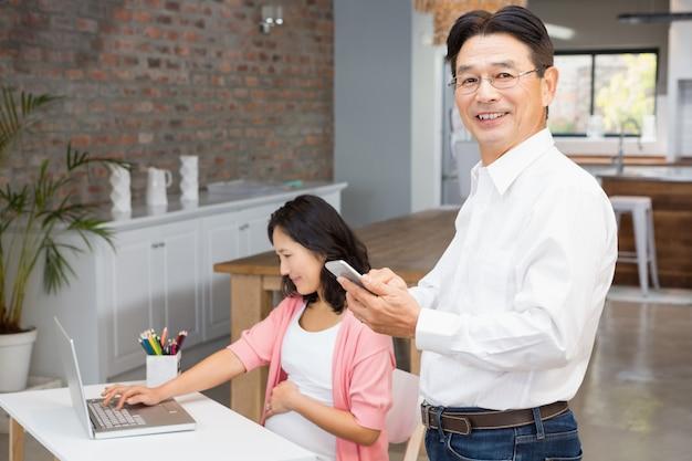 Homem feliz usando smartphone enquanto mulher grávida está usando o laptop em casa