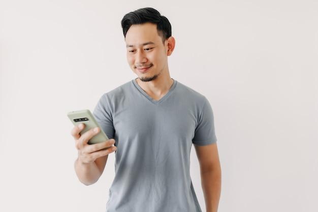 Homem feliz usando smartphone isolado no fundo branco