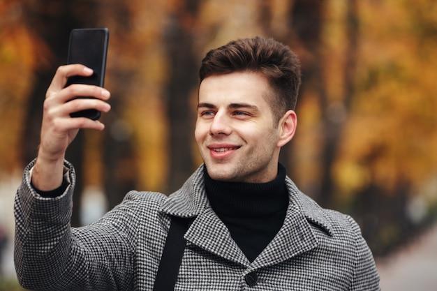 Homem feliz vestido calorosamente tirando foto da natureza ou fazendo selfie usando smartphone preto, enquanto caminhava no parque