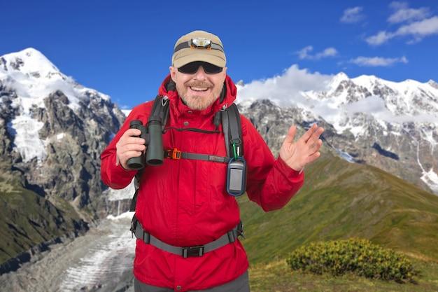 Homem feliz viajante com binóculos na mão em montanhas cobertas de neve