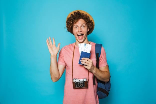 Homem feliz viajante com cabelos cacheados, usando mochila e chapéu de palha com passaporte e bilhetes