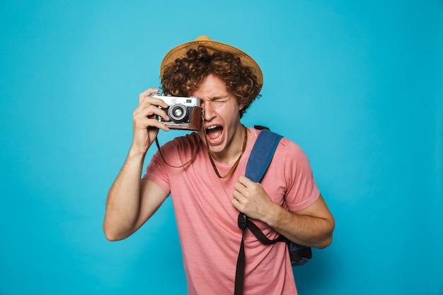 Homem feliz viajante com cabelos cacheados, usando mochila e chapéu de palha fotografando na câmera retro