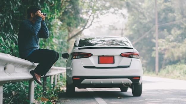 Homem feliz viajante na estrada com um carro branco e segurando a câmera.