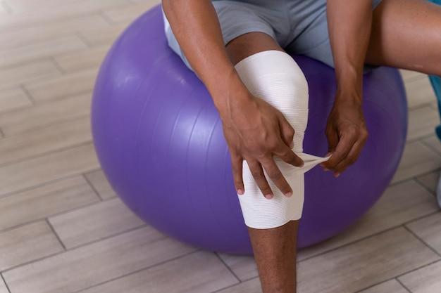 Homem ferido fazendo exercícios de fisioterapia para caminhar