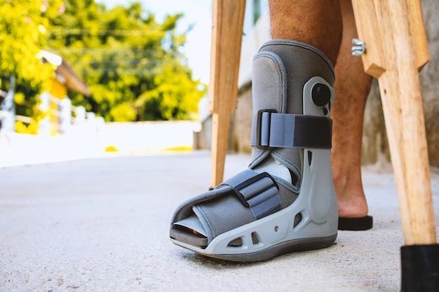 Homem ferido quebrado tornozelo usando suporte de tornozelo