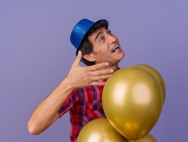 Homem festeiro de meia-idade impressionado com chapéu de festa em pé atrás de balões, segurando as mãos no ar, olhando para cima isolado na parede roxa