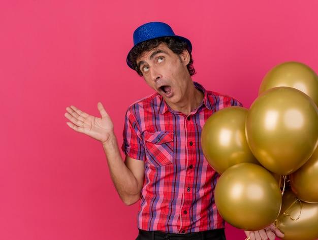 Homem festeiro de meia-idade impressionado com chapéu de festa segurando balões olhando para cima e mostrando a mão vazia isolada na parede vermelha