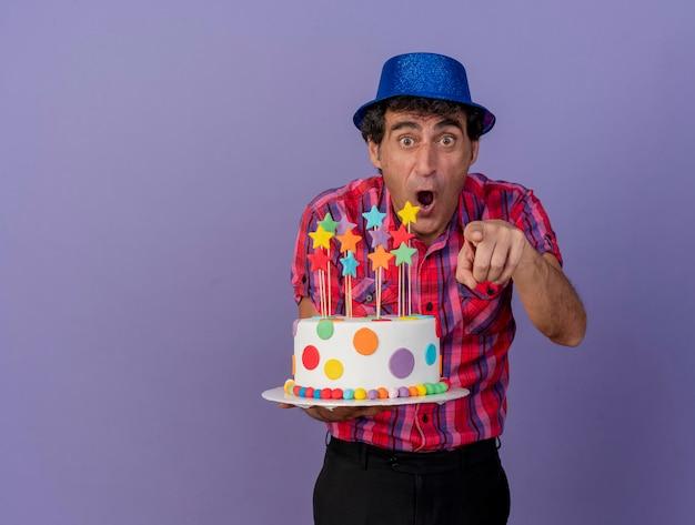 Homem festeiro de meia-idade impressionado com um chapéu de festa segurando um bolo de aniversário, olhando e apontando para a frente, isolado na parede roxa com espaço de cópia