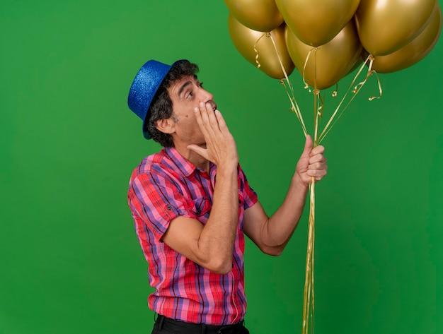 Homem festeiro de meia-idade impressionado em vista de perfil segurando balões, olhando para eles e sussurrando isolados na parede verde