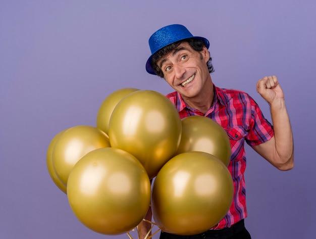 Homem festeiro de meia-idade sorridente com chapéu de festa segurando balões olhando para o lado fazendo gesto de sim isolado na parede roxa