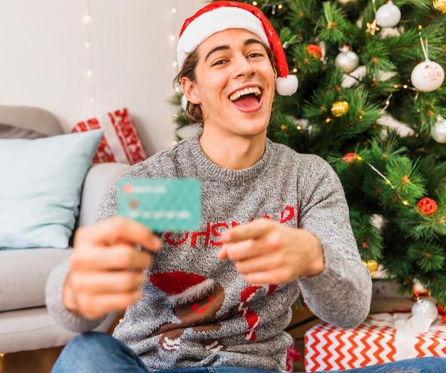 Homem festivo apontando para cartão de crédito