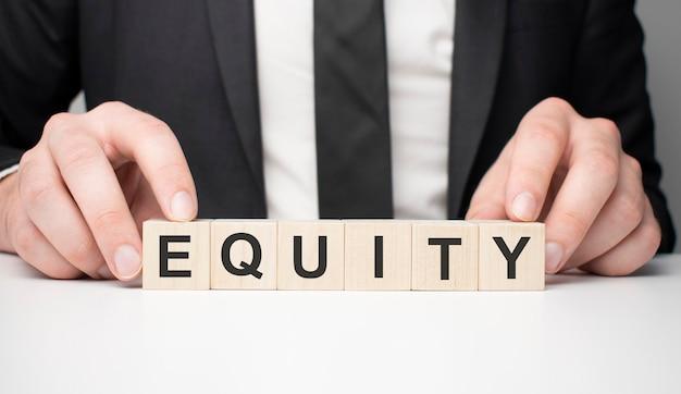 Homem fez palavra equidade com blocos de madeira. conceito de negócios.