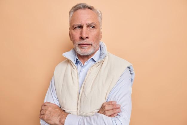 Homem fica de braços cruzados pensa em problemas pessoais perdido em pensamentos lembra e sente falta de algo usa camisa formal e colete isolado em bege