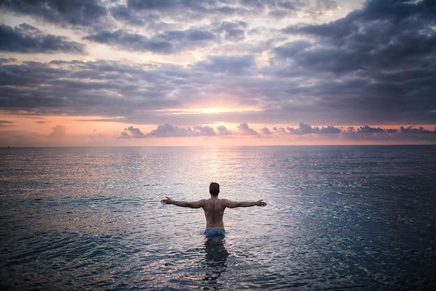 Homem fica na água do mar, voltado para o pôr do sol