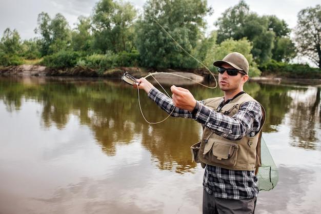 Homem fica na água e acenando com haste de mosca. ele vai pescar. cara tem rede de pesca nas costas. ele parece sério e calmo.