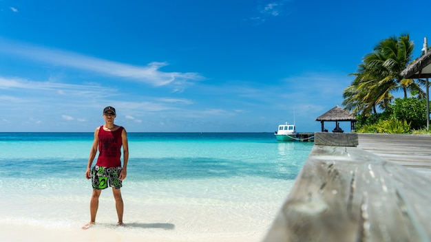 Homem fica na praia. ilha de luxo nas maldivas, cais de madeira no mar azul tropical.