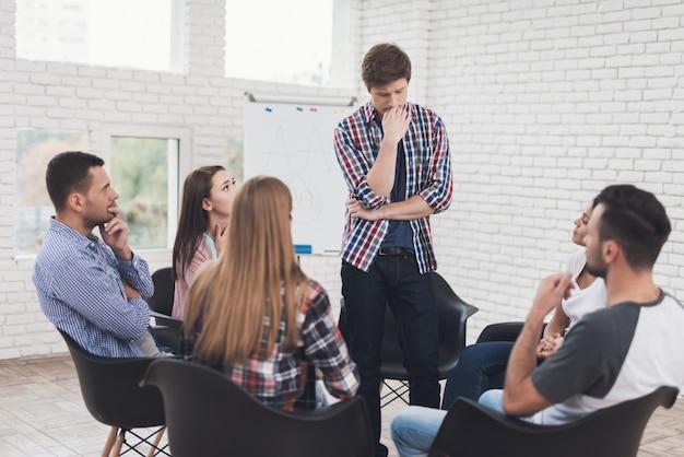 Homem fica no círculo de pessoas durante a sessão de terapia de grupo.