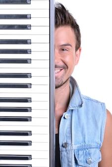 Homem fica no piano e sorri.