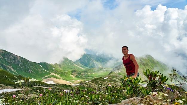 Homem fica no pico da montanha achisho, neve no verão sochi, rússia