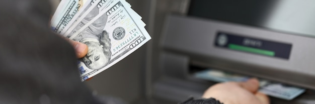 Homem fica perto do terminal e retira dólares em dinheiro. limite as retiradas de dinheiro durante a quarentena. retirada automatizada de dinheiro usando cartões de pagamento. pagamento de bens e serviços através de um caixa eletrônico