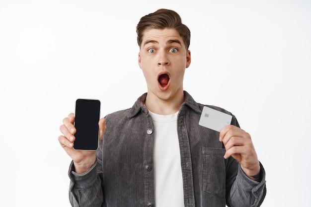 Homem fica surpreso, mostra a tela do smartphone e o cartão de crédito, compra online pelo celular, compra na internet em branco