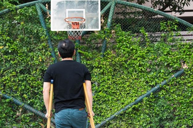 Homem, ficar, com, perna quebrada, em, gesso, elenco, usando, muletas, em, quadra basquetebol