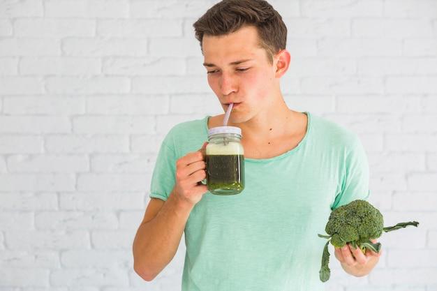 Homem, ficar, contra, branca, parede tijolo, bebendo, fresco, brócolos, smoothie, em, jarro