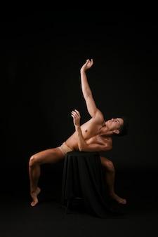 Homem, ficar, dedos pé, crouching, inclinar-se, cadeira