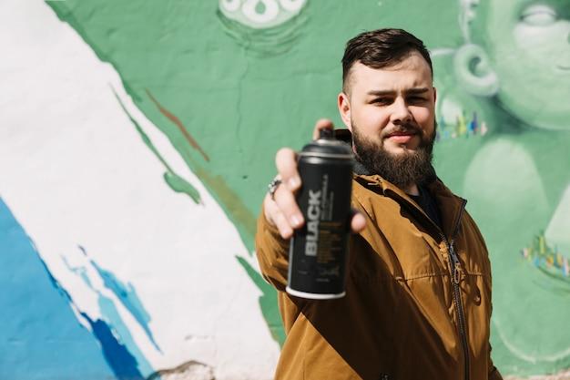 Homem, ficar, frente, graffiti, parede, com, lata aerossol, em, mão