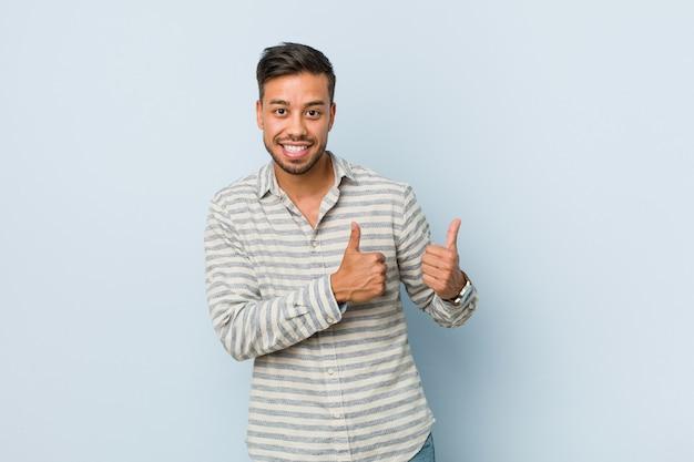 Homem filipino bonito jovem, levantando os dois polegares, sorrindo e confiante