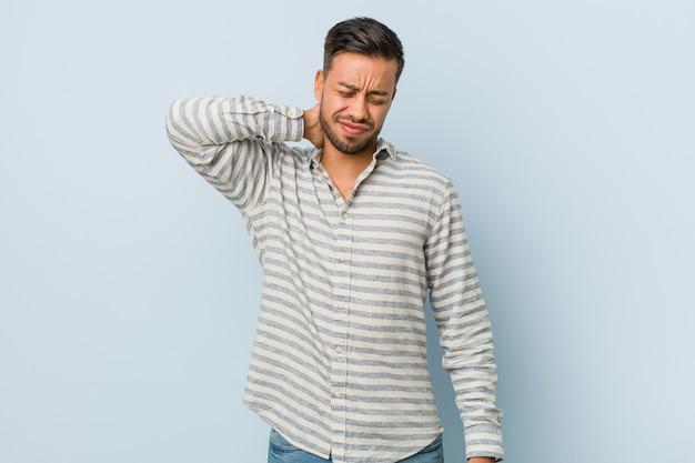 Homem filipino bonito jovem que sofre de dor de garganta devido ao estilo de vida sedentário.