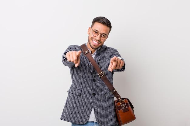 Homem filipino de negócios jovem contra um sorriso alegre de parede branca, apontando para a frente.