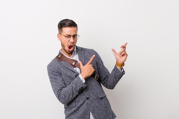 Homem filipino de negócios jovem contra uma parede branca, apontando com dedos indicadores para um espaço de cópia