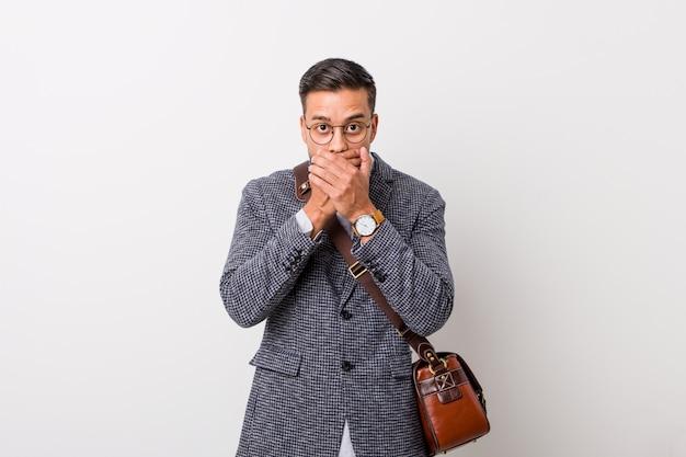 Homem filipino de negócios jovem contra uma parede branca chocado cobrindo a boca com as mãos.