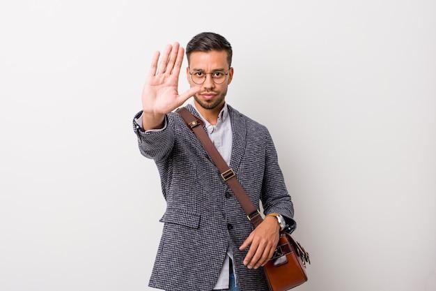 Homem filipino de negócios jovem contra uma parede branca de pé com a mão estendida, mostrando o sinal de stop, impedindo-o