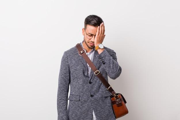 Homem filipino de negócios jovem contra uma parede branca, esquecendo algo, batendo na testa com a palma da mão e fechando os olhos.