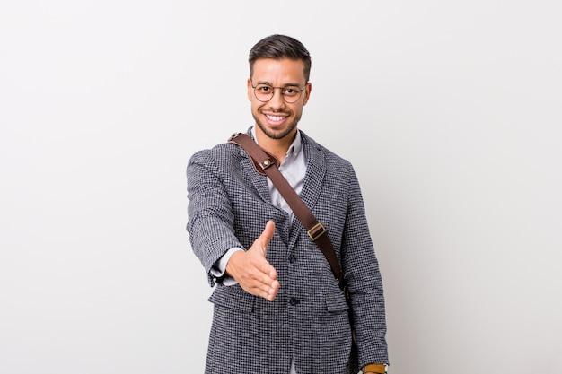 Homem filipino de negócios jovem contra uma parede branca, esticando a mão em gesto de saudação.