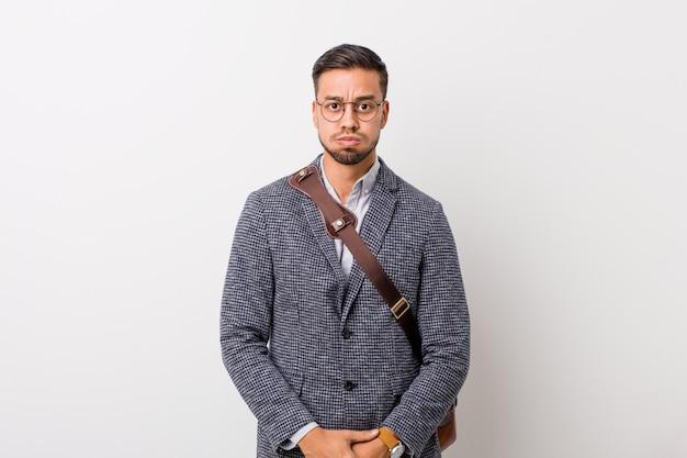 Homem filipino de negócios jovem contra uma parede branca sopra as bochechas, tem expressão cansada. expressão facial.