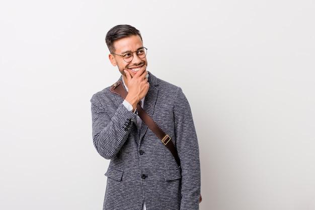Homem filipino de negócios jovem mantém as mãos sob o queixo, está olhando alegremente de lado