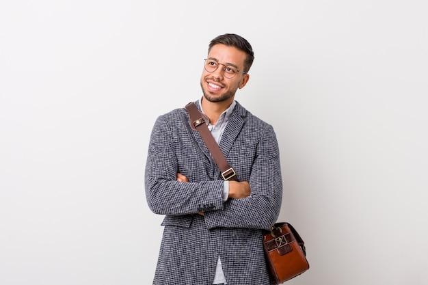 Homem filipino do negócio novo contra um sorriso branco da parede seguro com braços cruzados.