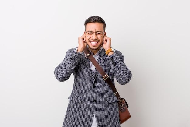 Homem filipino do negócio novo contra uma parede branca que cobre as orelhas com as mãos.