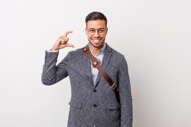 Homem filipino do negócio novo contra uma parede branca que mantém algo pequeno com o dedo indicador, sorrindo e seguro.