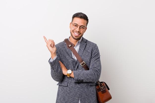 Homem filipino do negócio novo de encontro a uma parede branca que sorri alegremente apontando com dedo indicador afastado.