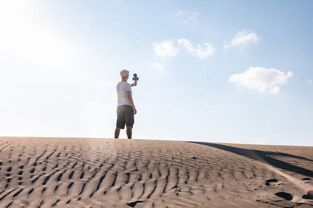 Homem filmando-se com seu telefone celular nas dunas do deserto, viajando criador de conteúdo masculino