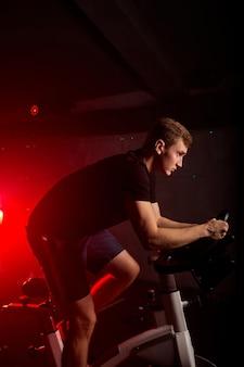 Homem fisicamente apto em um moderno centro de fitness, com agasalho, olhando para a frente durante o treino de bicicleta