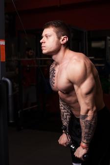 Homem fisiculturista realizando exercícios na academia