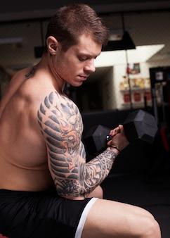 Homem fisiculturista realizando treinamento de bíceps