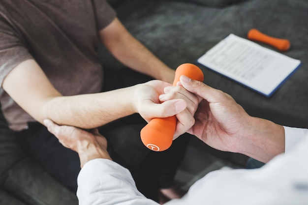 Homem fisioterapeuta dando exercício com tratamento com halteres sobre o braço e ombro apy conceito